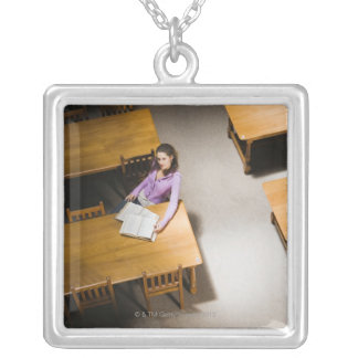 Woman reading book in library silver plated necklace