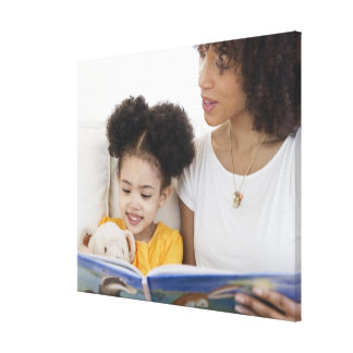 Woman reading book with daughter canvas print
