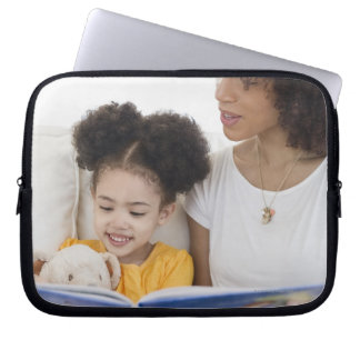 Woman reading book with daughter laptop sleeve