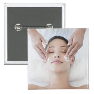 Woman receiving facial massage 15 cm square badge