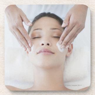 Woman receiving facial massage coaster