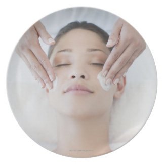 Woman receiving facial massage plate