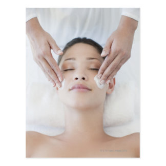 Woman receiving facial massage postcard