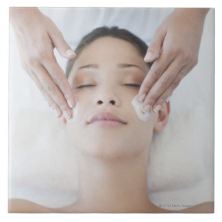 Woman receiving facial massage tile