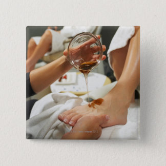 Woman receiving foot massage with oil 15 cm square badge