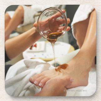 Woman receiving foot massage with oil coaster