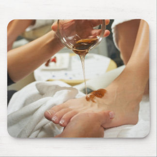 Woman receiving foot massage with oil mouse mat