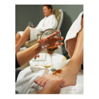 Woman receiving foot massage with oil postcard