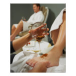 Woman receiving foot massage with oil poster