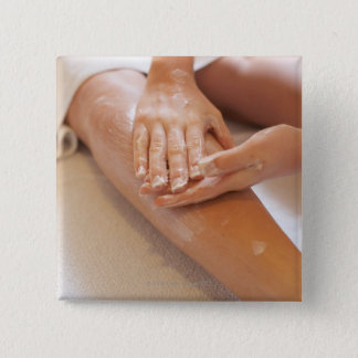 Woman receiving leg massage with lotion 15 cm square badge