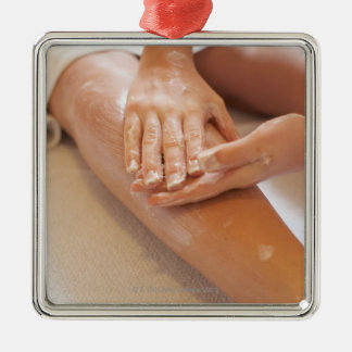 Woman receiving leg massage with lotion christmas ornament