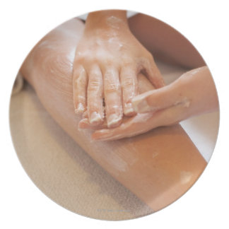 Woman receiving leg massage with lotion plate