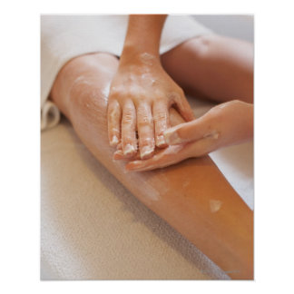 Woman receiving leg massage with lotion poster
