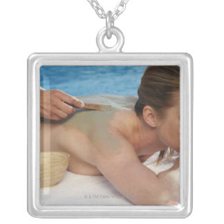 Woman receiving spa treatment, side view, close silver plated necklace