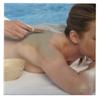 Woman receiving spa treatment, side view, close tile