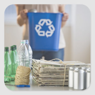 Woman recycling plastic bottles, cans and square sticker