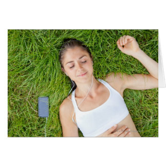Woman relaxes with music in soft grass greeting card