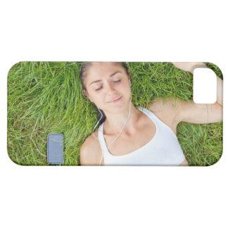 Woman relaxes with music in soft grass iPhone 5 covers
