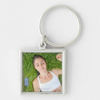 Woman relaxes with music in soft grass key ring