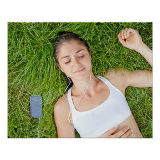 Woman relaxes with music in soft grass poster