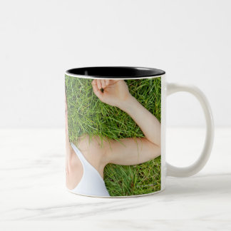Woman relaxes with music in soft grass Two-Tone coffee mug