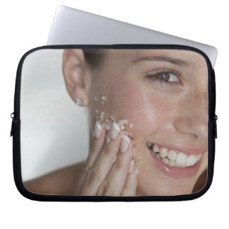 Woman scrubbing sugar on her face laptop sleeve