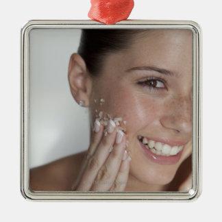 Woman scrubbing sugar on her face Silver-Colored square decoration