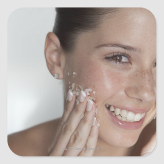 Woman scrubbing sugar on her face square sticker