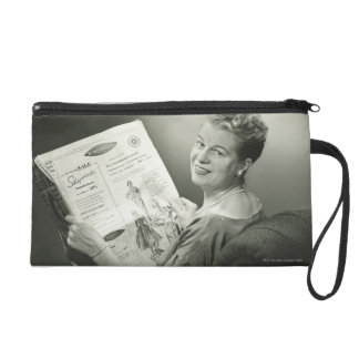 Woman Sitting in Chair Wristlet Clutches