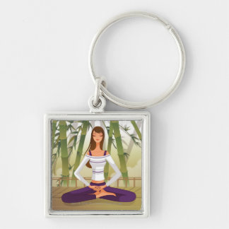 Woman sitting in lotus position, meditating key ring