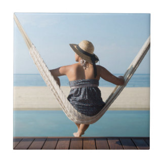 Woman Sitting On A Hammock At A Small Hotel Small Square Tile