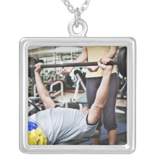 Woman spotting man lifting barbell pendant