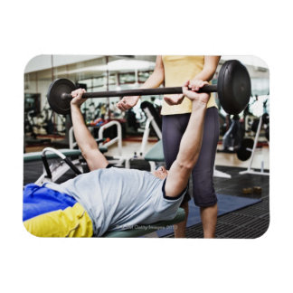 Woman spotting man lifting barbell rectangle magnets