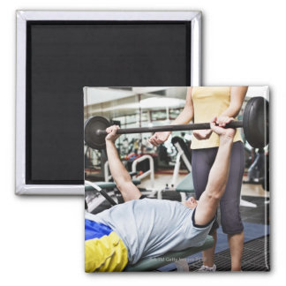 Woman spotting man lifting barbell square magnet