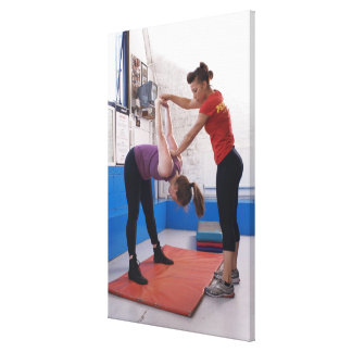 Woman stretching with trainer in gym canvas print