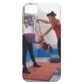 Woman stretching with trainer in gym iPhone 5 cover