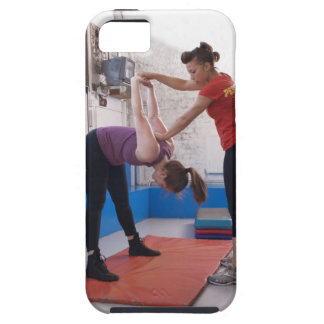Woman stretching with trainer in gym iPhone 5 cases