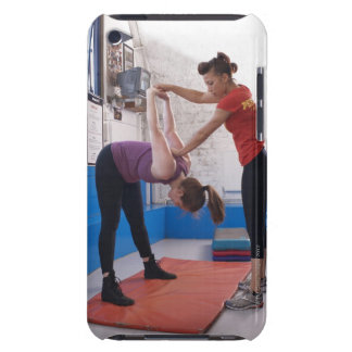 Woman stretching with trainer in gym iPod touch covers