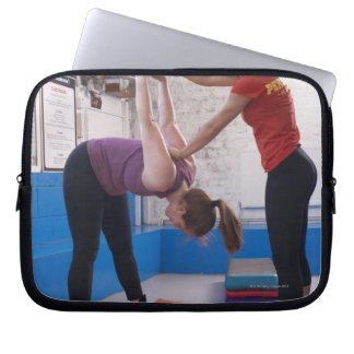 Woman stretching with trainer in gym laptop sleeve