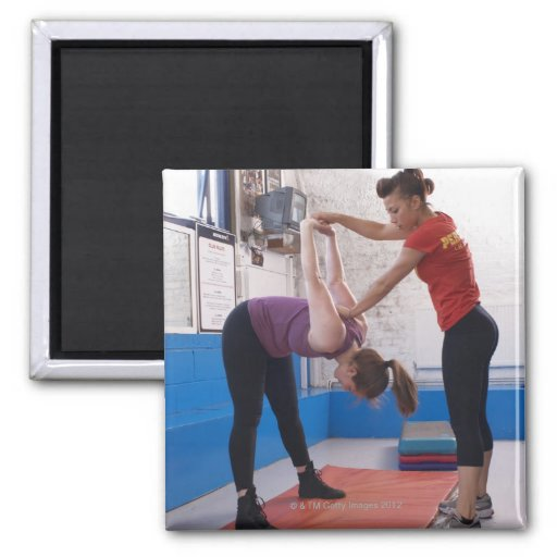 Woman stretching with trainer in gym fridge magnets
