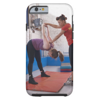 Woman stretching with trainer in gym tough iPhone 6 case