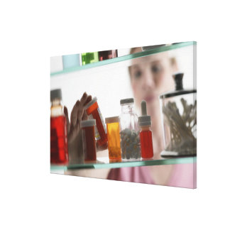 Woman taking pills from medicine cabinet canvas print