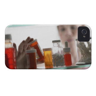 Woman taking pills from medicine cabinet iPhone 4 covers