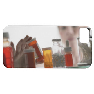 Woman taking pills from medicine cabinet iPhone 5 cover