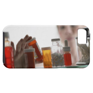 Woman taking pills from medicine cabinet iPhone 5 covers