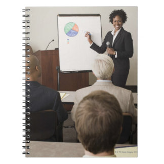 Woman teaching a class to adults notebook