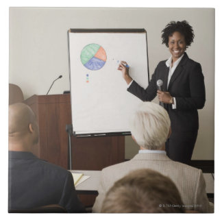 Woman teaching a class to adults tile