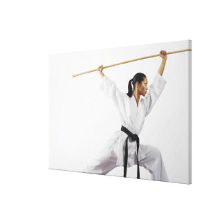 Woman using bow staff canvas print