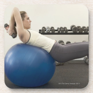 Woman using exercise ball and hand weights coaster