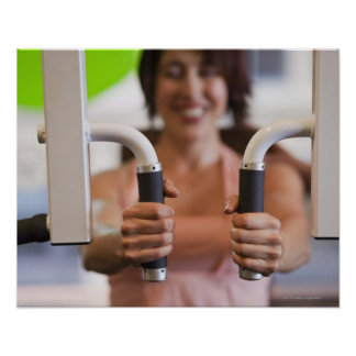Woman using exercise machine in gym poster